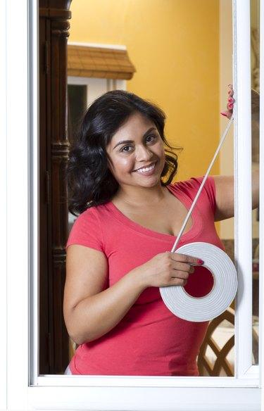 Energy Efficiency Hispanic Woman Applies Weather Stripping Vertical