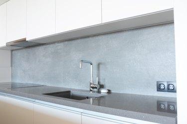 Modern kitchen with metal faucet, ceramic kitchen sink, kitchen stove, kitchen hood