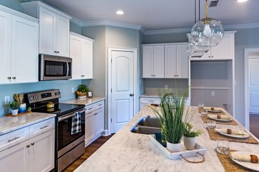 Open floor plan kitchen in a new construction empty house that has just been completed with white cabinets, pendant lighting, a bar area and hardwood floors
