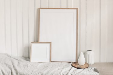 Portrait and square empty wooden frame mockups with linen cloth and modern ceramic vases. White beadboard wainscot wall paneling background. Scandinavian interior, home design. Art concept.