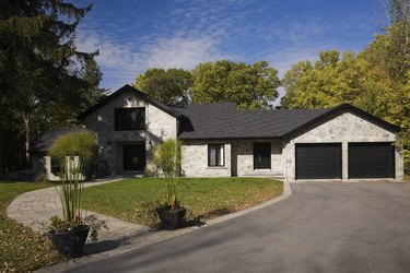 Grey stone luxury home with drive and garden