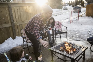 Family roasting marshmallows at fire pit in snowy driveway