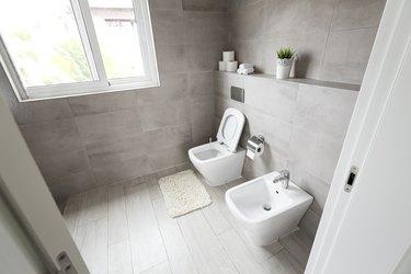 Half-open door to luxury bathroom with white ceramic bidet and toilet