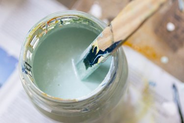 Stirring lightgreen paint.