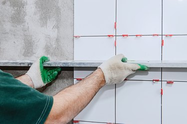 Ceramic tiles. The master lays ceramic tiles on the wall and draws them out using a special level.