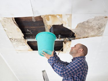 Man collecting water in bucket from ceiling.