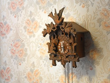 Vintage wooden cuckoo clock over a rose-pattern wall