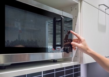 Woman's Hands pressing button on black microwave for cooking