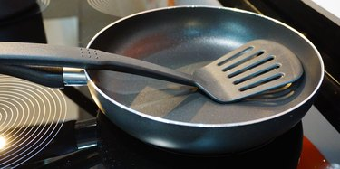 Metal black frying pan with a non-stick coating on electric stove