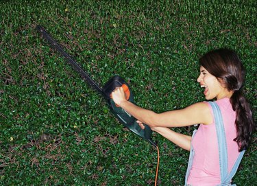 Woman with hedge trimmer.