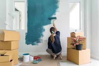 Young asian happy woman painting interior wall