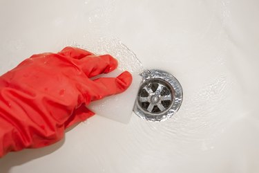 A hand in a red rubber glove with a melamine sponge rubs the white bathroom near the drain hole where the water flows