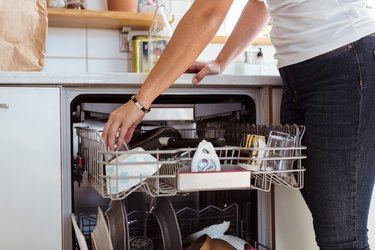 Midsection of woman using dishwasher while standing in kitchen