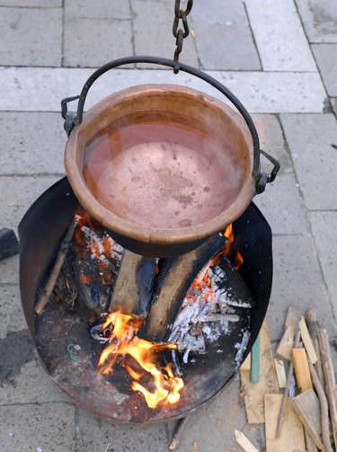 Cauldron with boiling water and a large wood fire