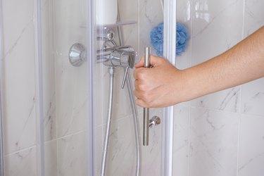 Woman hand opening shower door in domestic bathroom.