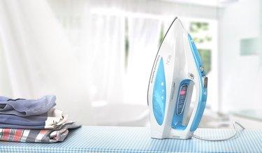 Iron on ironing board on room background