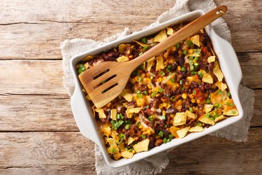 Crispy homemade frito pie with beef, cheese, corn, beans and chips close-up in a baking dish. Horizontal top view