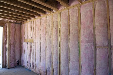 Wall of pink insulation in house