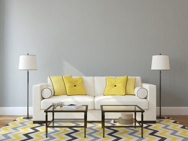 White sofa against gray wall with glass tables