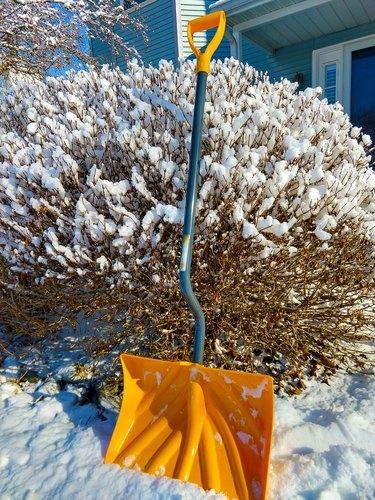 Snow shovel in snow.