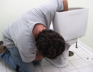 Plumber at work, man installing new toilet