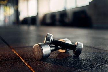 Dumbbells on rubber floor closeup, fitness club