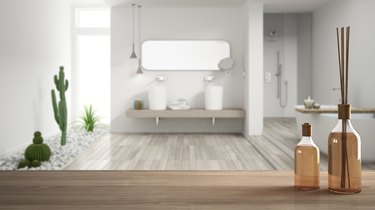 Wooden table top or shelf with aromatic sticks bottles over blurred modern bathroom with garden, white architecture interior design