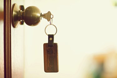 House key with home keyring in keyhole, property concept