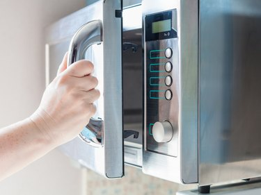 hand opens microwave oven for cooking food