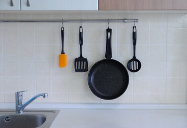 Frying pan with non-stick coating, a spatula for a steak, a spoon against the background of a tiled wall. The interior of the kitchen.