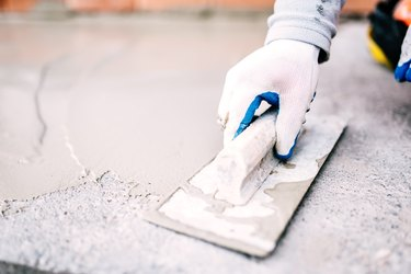 industrial worker on construction site laying sealant for waterproofing cement