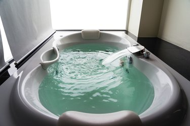 White massaging jetted bathtub with turquoise water and blank background