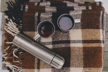 winter picnic on the snow. Hot tea, thermos on blanket.