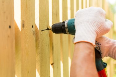 Hands of the carpenter holding electric screwdriver