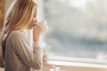 Profile view of pensive woman drinking morning coffee at home.