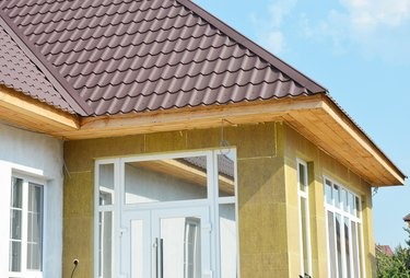 Install metal roof and rock wall insulation with unfinished soffits and fascia boards. House wall insulation.