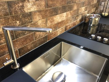 Image of rectangular kitchen butler sink, white stainless stee sink with black granite worktop countertop and composite modern induction ceramic hob / black kitchen cooker stove electric hot plate zones with touch control knobs