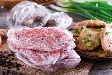 Frozen pork neck chops meat and pork schnitzel in a plate