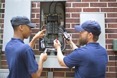 Repairmen, electricians working on home breaker box.