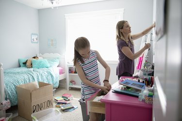 Mother and daughter cleaning room.