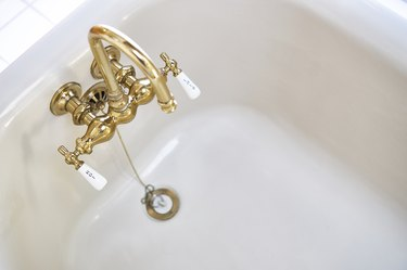 Vintage brass faucet in bathtub