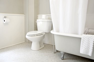 white toilet, white clawfoot tub with white shower curtain