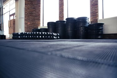 Ground view of a mat with weights and barbells in a gym