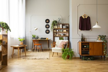 Armchair next to plant in vintage living room interior with wooden cabinet and chair at desk. Real photo