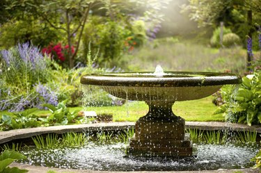Beautiful summer garden with water fountain in amongst the flowers, in the hazy sunshine