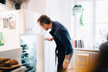 Mature man looking into refrigerator while standing at kitchen