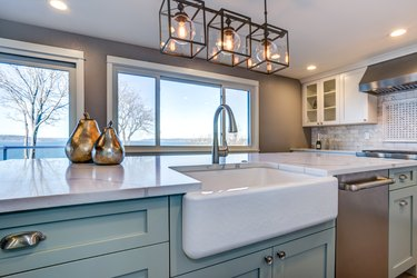 Beautiful kitchen room with green island and farm sink.