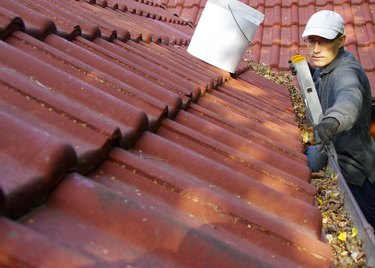 The man cleans the gutters on the roof