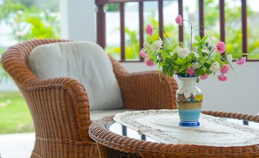 Weave chair with white pillow and flower vase with nature background