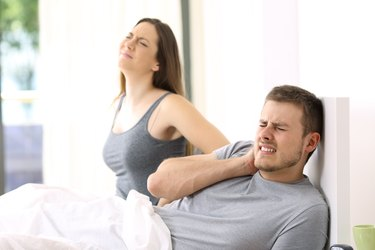 Couple suffering ache in an uncomfortable bed.